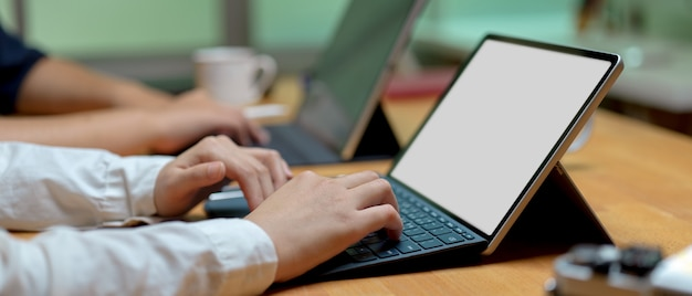 Arbeitnehmerin, die an ihrem projekt mit tablette arbeitet, während sie mit ihrem kollegen im büroraum sitzt