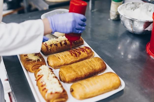 Arbeitnehmerin, die in einer großen bäckerei arbeitet. vorbereitung der brötchen.