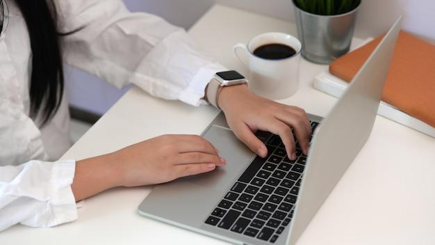 Arbeitnehmerin, die unter verwendung der laptoptastatur an ihrem arbeitsplatz schreibt