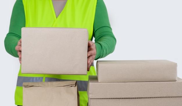 Arbeitnehmerin ist in einer grünen weste, die nahe viele papierboxen mit leerem auftrag, lieferkonzept steht.