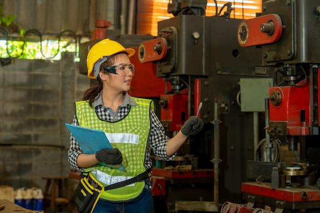 Arbeitnehmerinnen mit schutzhelm arbeiten in industrieanlagen mit maschinen.