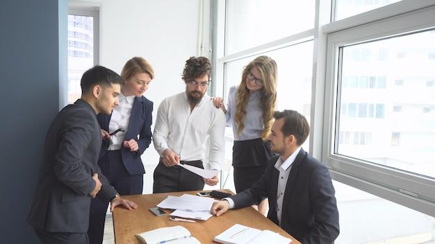 Arbeitsatmosphäre im büro. gruppe von geschäftsleuten, die geschäftsthemen diskutieren.