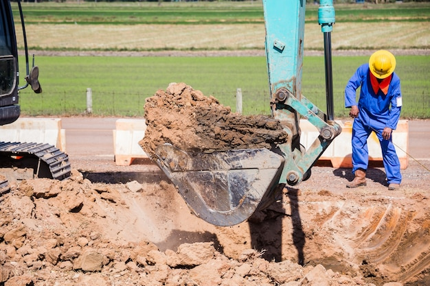 Arbeitsbagger-traktor, der einen graben graben.