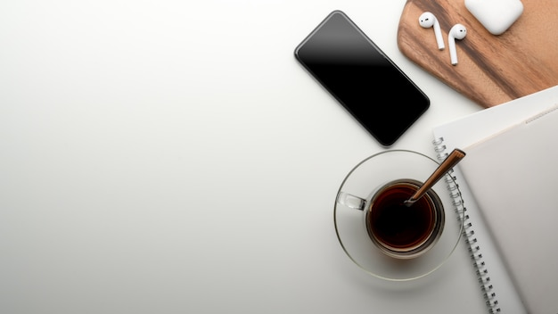 Arbeitsbereich am esstisch mit kopierbereich, smartphone, terminkalender, teetasse, kopfhörer auf holztablett