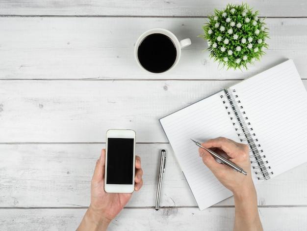 Arbeitsbereich auf weißem holztisch draufsicht kopienraumhand halten silbernen stift und smartphone in der hand