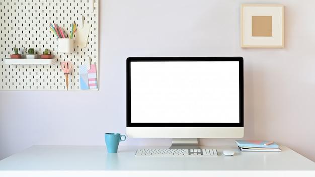 Arbeitsbereich computer, der auf weißem schreibtisch zusammen bürozeug und steckbrett mit kaffeetasse, pastellkonzept setzt.