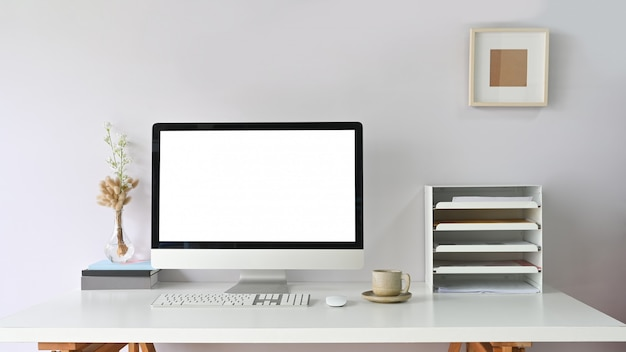 Arbeitsbereich computermonitor mit weißem leerem bildschirm auf schreibtisch und umgeben von bücherregal, maus, tastatur, kaffeetasse.