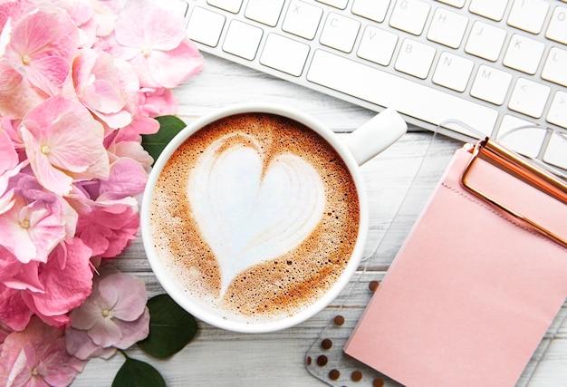 Arbeitsbereich des hauptbüroschreibtischs mit rosa hortensienblumenstrauß, tasse kaffee und tastatur auf weißem hölzernem hintergrund. flatlay, draufsicht.