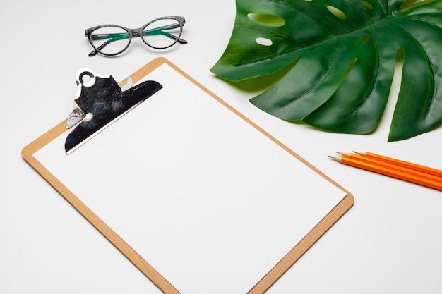 Arbeitsbereich für das büro zu hause mit zwischenablage, palmblatt und zubehör. flachgelegt, draufsicht