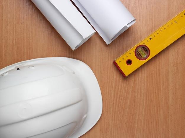 Arbeitsbereich für ingenieure. bauhelm, rollen mit zeichnungen, waagerecht auf dem tisch. draufsicht.