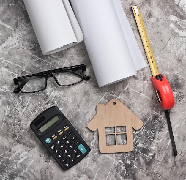 Arbeitsbereich für ingenieure. bauhelm, zeichnungsrollen, taschenrechner und brille, lineal auf grauem betonhintergrund. hausbau. draufsicht.