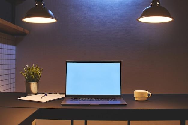 Arbeitsbereich für remote-online-arbeit an einem laptop mit leerem weißen bildschirm in einem modernen loft-interieur