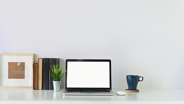 Arbeitsbereich laptop-computer, buch, fotorahmen und kaffeetasse mit blumentopf auf kopie raum weißen tisch.