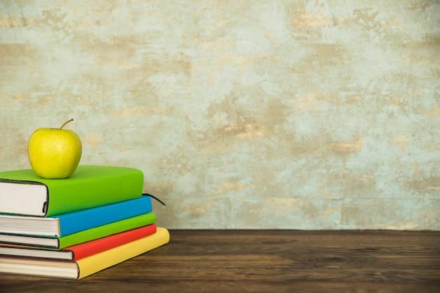Arbeitsbereich mit büchern und grünem apfel