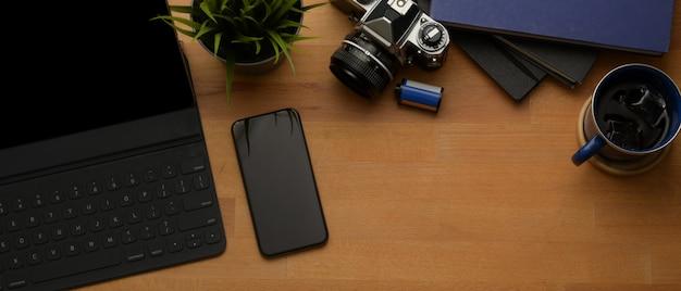 Arbeitsbereich mit digitalem tablet, smartphone, kamera, notebooks, kaffeetasse und kopierbereich auf holztisch