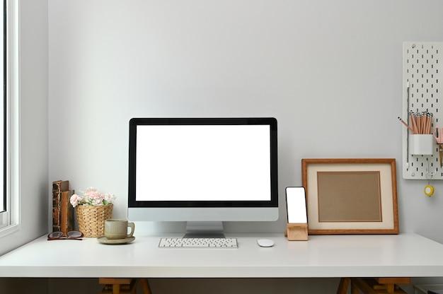 Arbeitsbereich mit einem desktop-computer mit weißem bildschirm und einem smartphone auf einem weißen tisch