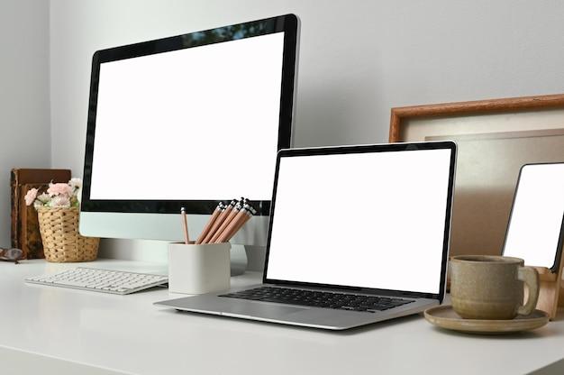 Arbeitsbereich mit einem modell-pc-pc mit leerem bildschirm und laptop auf weißem tisch