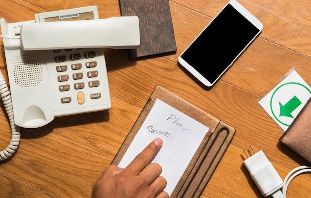 Arbeitsbereich mit erfolg plan in händen, telefon, smartphone, ladegerät, draufsicht