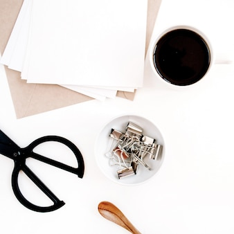 Arbeitsbereich mit kaffee, bastelumschlag, schere, papierrohling auf weißer oberfläche