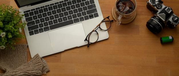 Arbeitsbereich mit laptop, kamera, brille, kaffeetasse, dekoration und kopiertempo auf holzschreibtisch