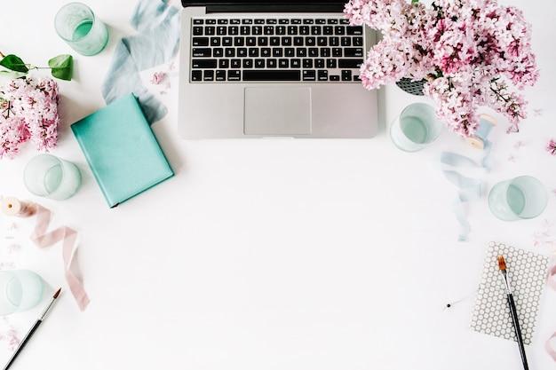 Arbeitsbereich mit laptop, lila blumenstrauß und tagebuch
