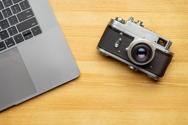 Arbeitsbereich mit laptop und kamera auf holztisch. draufsicht