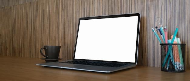 Arbeitsbereich mit leerem bildschirm des laptops, kaffeetasse, briefpapier auf hölzernem schreibtisch.