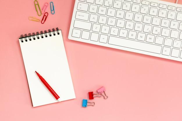 Arbeitsbereich mit leerem gewundenem notizbuch mit tastatur auf koralle