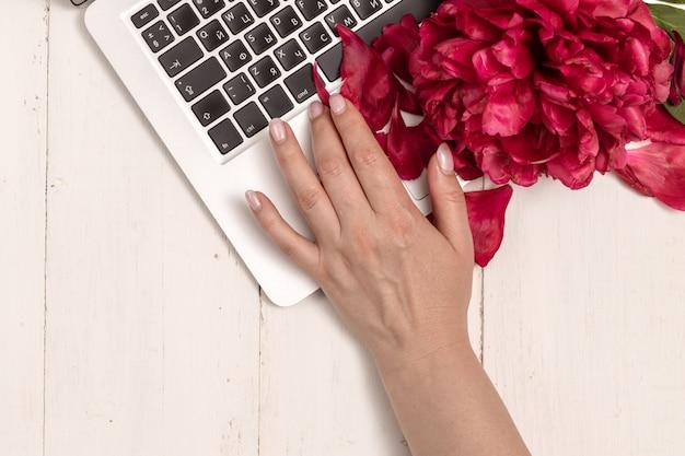 Arbeitsbereich mit mädchenhand auf laptop-tastatur