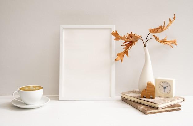 Arbeitsbereich mit nachgebildetem weißem holzplakatrahmen, kaffeetasse, philodendron getrocknetem blatt in vasenuhr bücherhausmodell auf beigem tisch