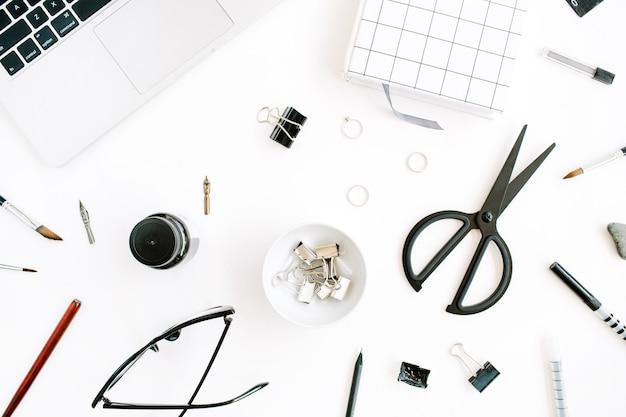Arbeitsbereich mit notebook, laptop, schere, brille, stift auf weiß.