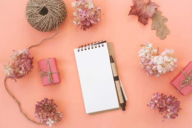 Arbeitsbereich mit notizbuch auf pfirsichhintergrund