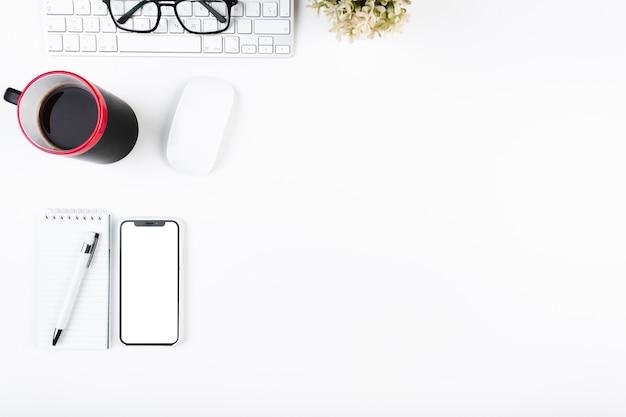 Arbeitsbereich mit smartphone becher und tastatur