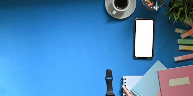 Arbeitsbereich mit smartphone, kaffee und büromaterial mit kopierraum.