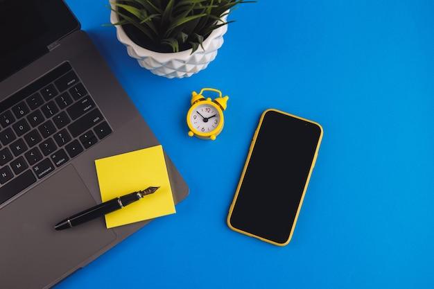 Arbeitsbereich mit stift, uhr, haftnotiz und laptop. unternehmensfinanzierung, bildungskonzept.