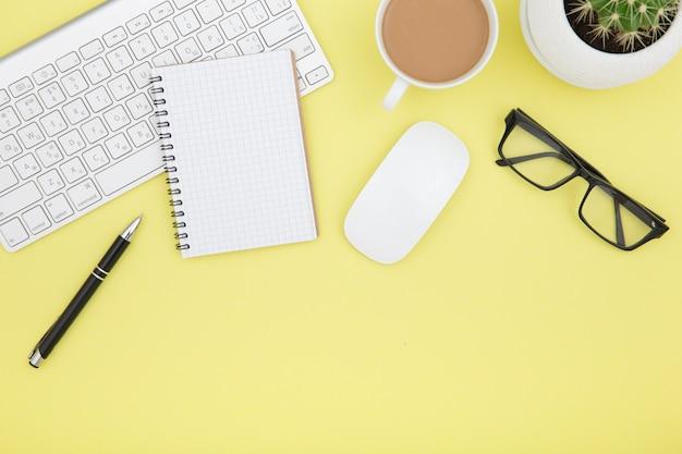 Arbeitsbereich mit tablet, tastatur, kaffeetasse und brille