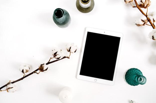 Arbeitsbereich mit tablette des leeren bildschirms und baumwolle auf weißem hintergrund. flache lage, ansicht von oben