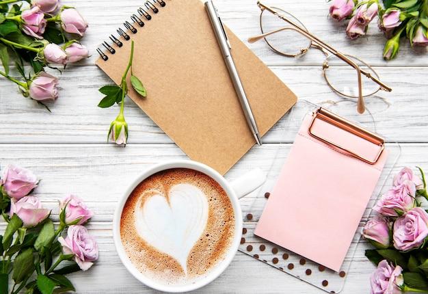 Arbeitsbereich mit tagebuch, notizbuch, zwischenablage, rosen auf weißem hintergrund. home-office-schreibtisch. draufsicht weiblicher hintergrund. flache lage, draufsicht.