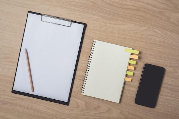 Arbeitsbereich mit tagebuch oder notizbuch und smartphone, zwischenablage, bleistift, haftnotizen