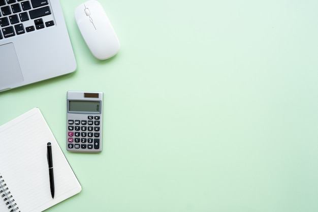 Arbeitsbereich mit taschenrechner, stift, laptop, notiz auf dem pastellgrünen hintergrund.