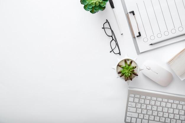 Arbeitsbereich mit tastatur-maus-brille papiere grünpflanzen. flache lage weißer schreibtisch home-office-arbeitsplatz-pc-computer. draufsicht des weißen tischbüros mit kopienraum.