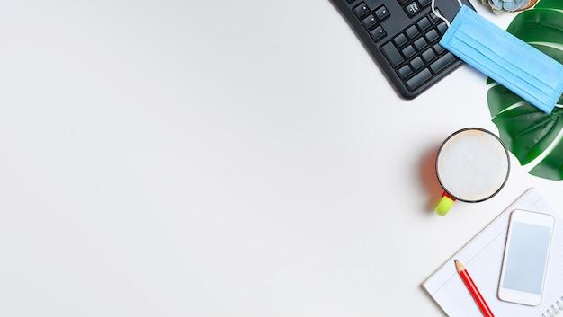 Arbeitsbereich mit tastatur, notizblock und einer tasse cappuccino-kaffee und blütenblättern. flach liegen