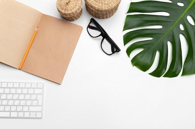 Arbeitsbereich mit tastatur, palmblatt und zubehör. flache lage, draufsicht copyspace