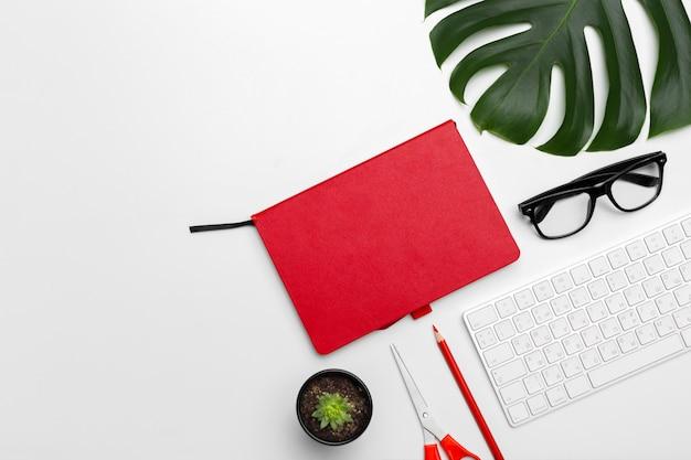 Arbeitsbereich mit tastatur, palmblatt und zubehör. flache lage, draufsichtkopienraum