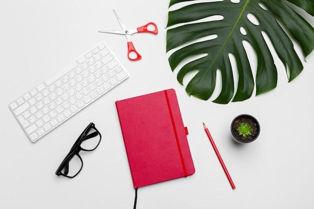 Arbeitsbereich mit tastatur, palmblatt und zubehör. flachgelegt, draufsicht
