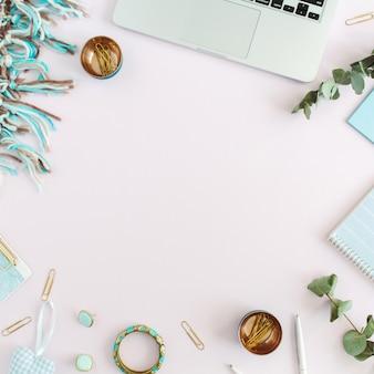 Arbeitsbereich von laptop, plaid, zwischenablage, zubehör auf rosa hintergrund. flache lage, ansicht von oben