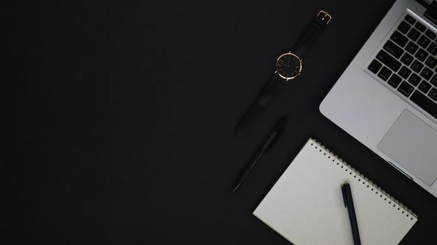 Arbeitsbereich von oben mit laptop-stiftuhr und schwarzem notizbuch