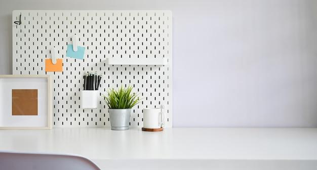 Arbeitsbereichbüroartikel und pegboard auf weißem tabellenkopienraum.