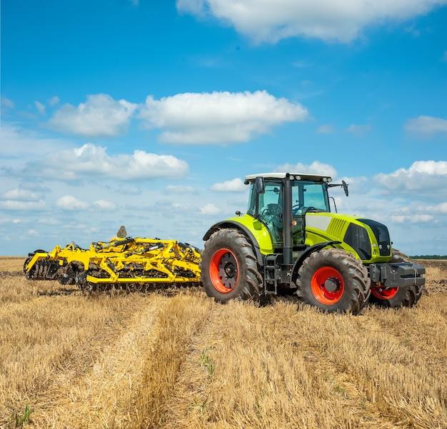 Arbeitsbereiter neuer grüner traktor mit scheibenegge zur vorbereitung des bodens für die aussaat einer neuen ernte
