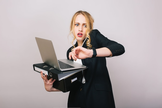 Arbeitsbüro beschäftigt zeit der blonden jungen frau in der formellen kleidung mit laptop, ordner, der am telefon spricht. erstaunt, arbeitend, beruflich, sekretär, büroangestellter, manager